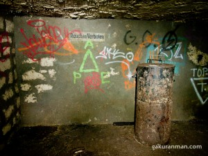 "A photo of the Nazi bunker beneath Paris, containing a German ""no smoking"" sign and an oil drum"